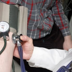 GP carrying out blood pressure exam